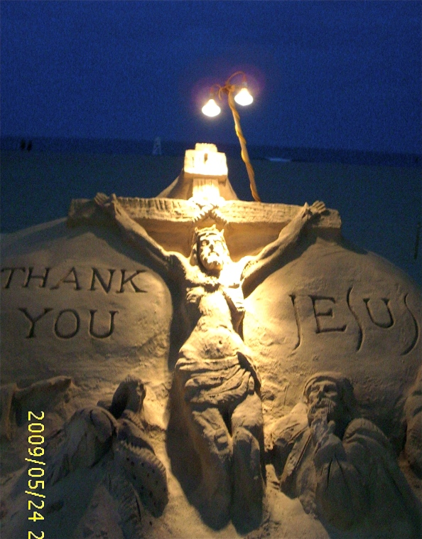 An image of Jesus Christ crucified. The sand art is lighted for viewing at night.