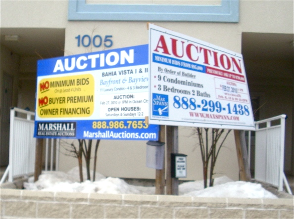 Two auction comopanies. Competing signs. Different terms of sale. Go figure.