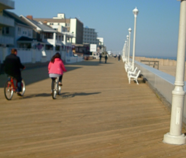 People bicycling and strolling on the fresh, new stretch of boardwalk between 12th and 14th Streets.