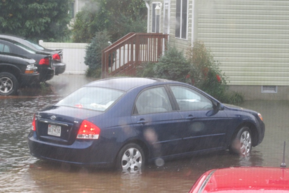 A car navigates a flooded West Ocean City Street shortly after high tide Monday morning.